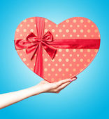 Hand holding shape heart box on blue backgorund — Stock Photo