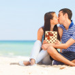 Young couple with gift on the beach in summer day. — Stock Photo #47300031