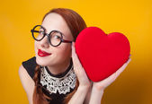 Nerd redhead girl with heart shape on yellow backgorund. — Stock Photo