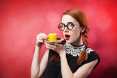 Redhead girl with cup of coffee on red background. — Stock Photo