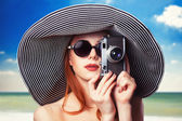 Redhead girl with retro camera on the beach — Stock Photo