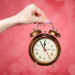 Hand holding alarm clock on red background. — Stock Photo #47407783