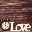 Clock with word love on wooden table. — Stock Photo #47407813