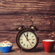 Cup of coffee and cupcake with alarm clock on wooden table. — Stock Photo #47407815