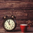 Cup of coffee and alarm clock on wooden table. — Stock Photo #47407823