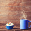 Cupcake and cup of coffee on wooden table. — Stock Photo