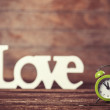 Clock with word love on wooden table. — Stock Photo