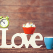 Cupcake, coffee, alarm clock and word Love on wooden table. — Stock Photo #47408115