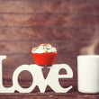 Cupcake, coffee and word Love on wooden table. — Stock Photo