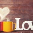 Two cups, abstract heart and word Love on wooden table. — Stock Photo #47408219