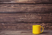Cup on wooden table and with wood on background — Stock Photo