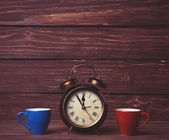 Two tea cup and alalrm clock on wooden table. — Stockfoto