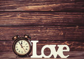 Clock with word love on wooden table. — Foto de Stock