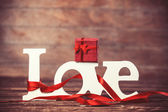 Little gift and word Love on wooden table. — Stock Photo