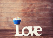 Cupcake and word Love on wooden table. — Foto Stock