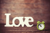 Clock with word love on wooden table. — Stockfoto