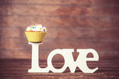 Cupcake and word Love on wooden table. — Стоковое фото