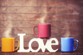 Three cups of coffee and word love on wooden table. — Stok fotoğraf