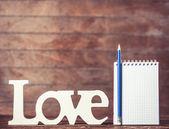 Lápiz y cuaderno con la palabra amor sobre fondo de madera. — Foto de Stock