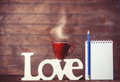 Cup of coffee with word Love and notebook on wooden background. — Stock Photo