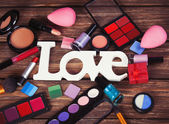 Cosmetics and word Love on wooden table — Stock Photo