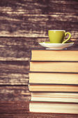 Books and cup of coffee on wooden background. — Stock Photo