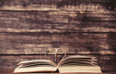 Vintage old books with heart shape on wooden table — Photo
