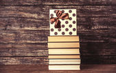 Gift and books on wooden table. — Stock Photo