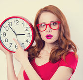 Surprised redhead girl with huge alarm clock on light background — Stock Photo