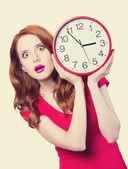 Förvånad rödhårig tjej med enorm väckarklocka på ljus bakgrund — Stockfoto