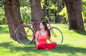Happy girl in the park with bicycle on background. — Stock Photo