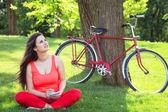 Brünette mädchen mit notebook im park und mit fahrrad auf rückseite — Stockfoto