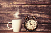 Tea or coffee cup and alarm clock — Stock Photo