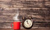 Tea or coffee cup and alarm clock — Stock Photo