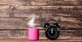 Taza de té o café y reloj despertador — Foto de Stock