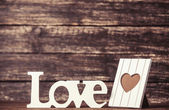 Word Love and frame for photo on wooden table. — Stock Photo