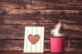 Frame with heart shape and cup of coffee on wooden background. — Stock Photo