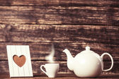 Teapot and cup of coffee with frame on wooden table. — Stock Photo