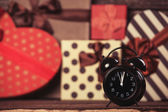 Alarm clock and gifts on background. — Stock Photo