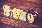 Alarm clock and word Love on wooden table. — Stock Photo