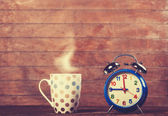 Cup of coffee and alarm clock on wooden table. — Foto de Stock