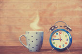 Cup of coffee and alarm clock on wooden table. — Stock Photo