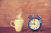 Cup of coffee and alarm clock on wooden table. — Foto Stock