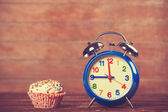 Cupcake with alarm clock on wooden table. — Stock Photo