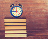Alarm clock and books on wooden table. — Stock Photo