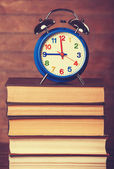 Alarm clock and books on wooden table. — Foto de Stock