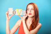 Mavi arka plan üzerinde kelime aşk ile sürpriz Kızıl saçlı kadın. — Stok fotoğraf