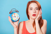 Surprised redhead women woth alarm clock on blue background. — Stock Photo