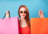 Style redhead women holding shopping bags on blue background. — Stock Photo