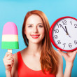 Redhead girl with toy ice cream and huge clock on blue backgroun — Stock Photo #48815345